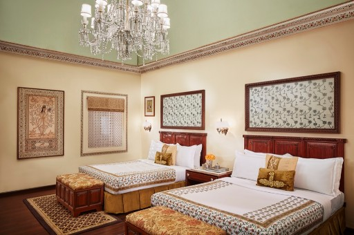 Antique crystal-framed mirrors set the theme of this suite. Around one is a panel of delicate scalloped arches painted in the â  Arayishâ   work Jaipur was famed for. A crystal chandelier and classical Indian paintings the dazzling picture.